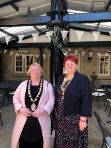 Mayor Mary Kelly stood with deputy Mayor in an outdoor eating space with bunting, both smiling.