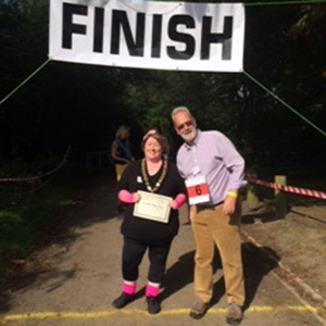 Mayor Mary Kelly with pink wrist and leg warmers, stood next to David Holmes, Town Proper Officer, at the finish line of a race event.