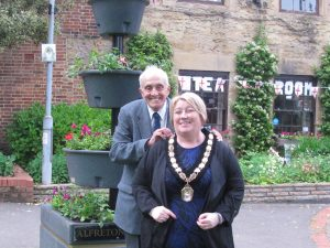 Councillor John Walker with his hands on the shoulders of Mayor Mary Kelly, both smiling, in front of some Alfreton town council flowers.