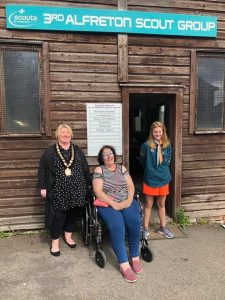 Mayor Mary Kelly standing on the left, a lady in a wheelchair in the centre and a girl from the scouts on the right, stood in front of the 3rd Alfreton Scout Group Hut.