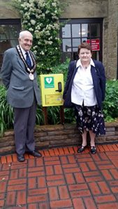 Mayor John Walker on the left, a smartly-dressed lady on the right, with a new defibrillator in the centre.