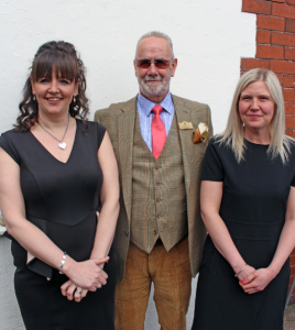 From left to right: Tina Crookes: Joint Town Clerk, David Holmes: Town Proper Officer, Vic Johnstone: Assistant Town Clerk. All standing together smiling.